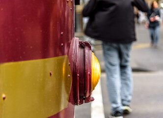 A close view of the front light of a Melbourne, Australia, city circle tourist tram with pedestrians in the background.