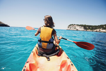 Young woman kayaking in the sea. Active lifestyle and travel concept