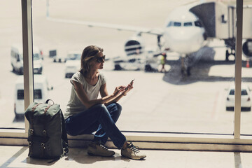 Young woman using smartphone in the airport, travel, vacations and active lifestyle concept