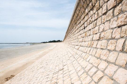 digue île de ré marée océan vague tempête construction sable retenir montée eau marche mur pierre béton changement climatique boutillon
