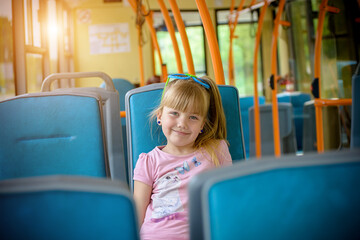 A little girl is going by bus