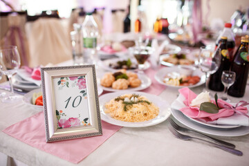 Frame with number ten stands on the dinner table