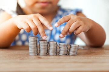 Cute asian little girl playing with coins making stacks of money,kid saving money for the future concept
