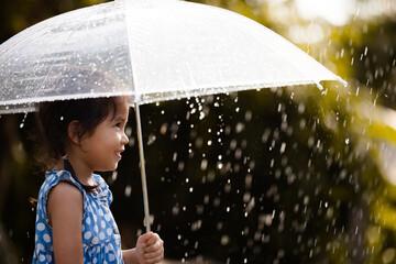 Portrait of cute asian little girl with umbrella in rain