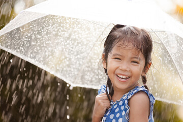 Happy asian little girl with umbrella in rain in vintage color tone