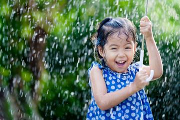 Happy asian little girl with umbrella in rain