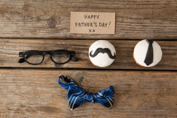 Happy fathers day text on paper and cupcakes