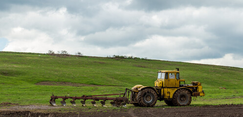 The tractor plows the land in the fields in the spring