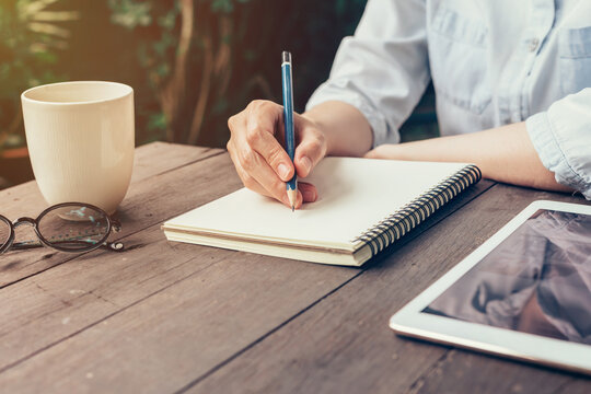 Woman hand writing note pad on wood table in coffee shop.
