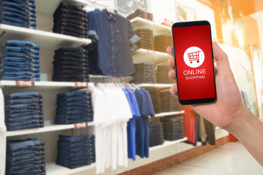 human hand hold smartphone, tablet, cell phone with shop cart online shopping on blurry Clothes shop.