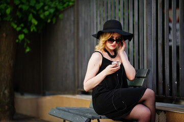 Blonde woman on black dress, sunglasses, necklaces and hat sitting on bench with mobile phone at hand and headphones.