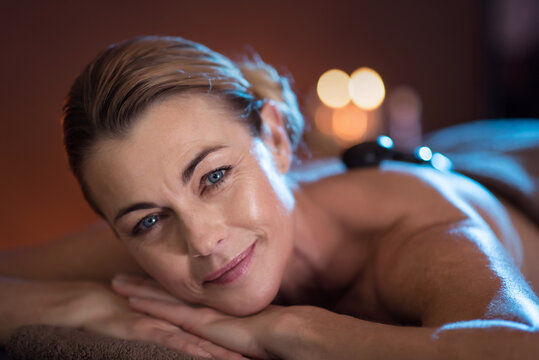 a woman lying on a massage table with hot stones on her back