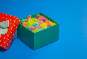 Mixed colorful candies, gift and jelly on copy space background.