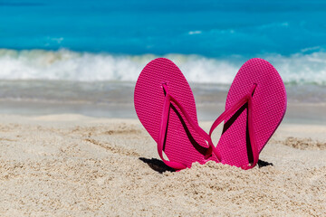 Flip flops on the sandy ocean beach , tropical vacation concept