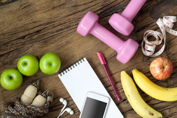 Fitness, healthy and active lifestyles Concept, dumbbells, smartphone, earphone, measuring tape, jump rope, bananas and apples on wood background. Top view with copy space.