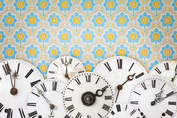 Collection of ancient clock faces in front of retro wallpaper