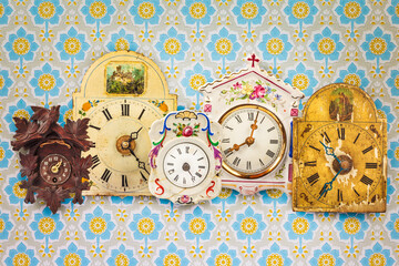 Collection of colorful hanging clocks in front of retro wallpaper