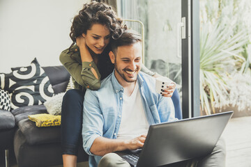 Portrait of a smiling young couple using laptop at home indoor
