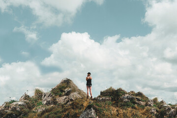 Young Woman standing on top of a mountain