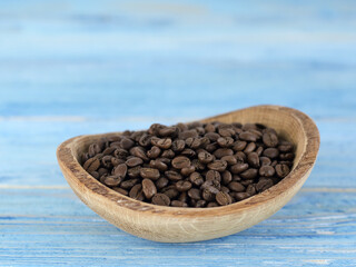 Natural coffee beans on a blue wooden board.