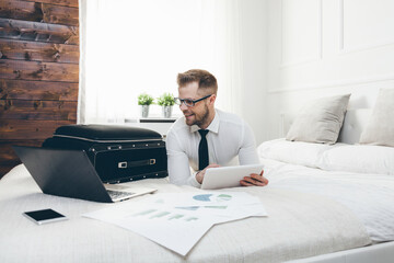 Businessman on bed working with a tablet and laptop from his hotel room