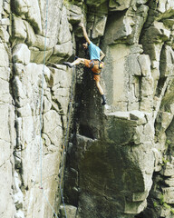 A young man climbs in a canyon.