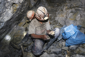 Potosi, Bolivia - November 29, 2013: Two miners looking for silver in the silver mine of the Cerro Rico in Potosi, Bolivia.