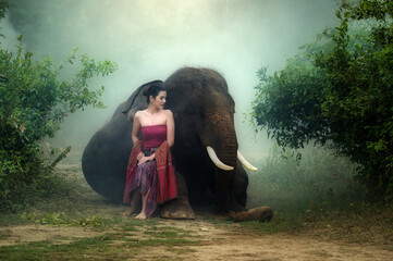Portrait beautiful asia woman in local traditional dress with elephant in wild at Thailand.