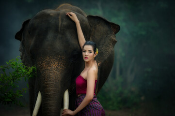 Thai beautiful women in traditional dress and elephant in wild