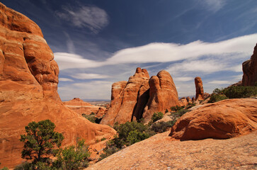 Sandstone formations in Arches National Park under partly cloudy skies.