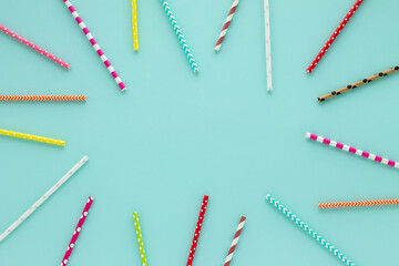Drinking straws for party on blue pastel background with copy space.