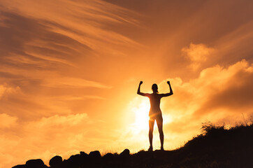 Winning and success concept. Silhouette of strong confident woman flexing outdoors.