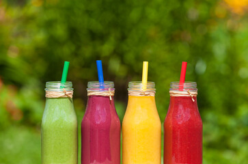 Assortment of healthy smoothie shakes, greens, berries and fruit juice.