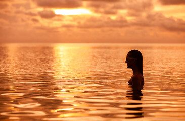 Relaxing beach holiday.  Girl going for a swim during a beautiful sunset.