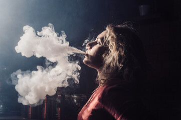Young, beautiful girl smokes a hookah. It produces smoke from his mouth. The pleasure of smoking.