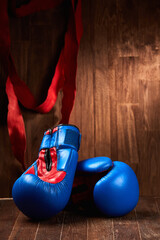 Two blue and red boxing gloves and red bandage against wooden background.