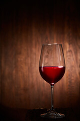 Half-full fragile wineglass of red wine standing on a wooden background.