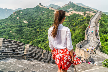 Wall Mural - Young girl tourist from behind looking at view of Great Wall of china at famous Badaling tourism attraction during travel vacation in Beijing. Asia summer holidays.