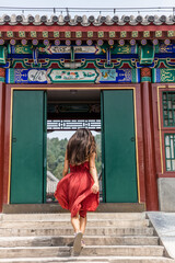 Elegant woman walking through old wooden traditional chinese gate at ancient imperial temple, china summer travel. Gorgeous girl with flowing hair and fashion red dress in the wind.