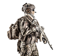 Operator of Russian special operations forces with kalashnikov assault rifle, military backpack and combat helmet. Studio shot, isolated on white background, profile view, half length