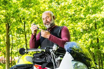 Mature, diabetic man testing his blood sugar beside his motorcycle