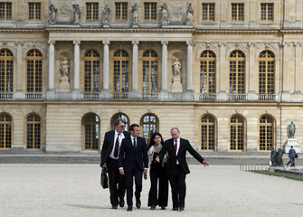 French President Emmanuel Macron and Russian President Vladimir Putin (R) followed by their interpreters, walk in the garden of the Versailles Palace following their meeting in Versailles