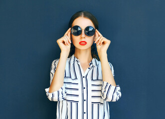 Fashion portrait of elegant woman lady in a black sunglasses posing over a gray background