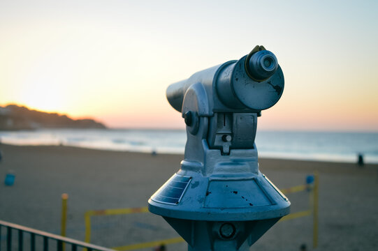 Touristic payment observation monocular pointing at the ocean shoreline sunset outdoors background