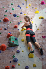 Woman practicing at indoor rock climbing gym