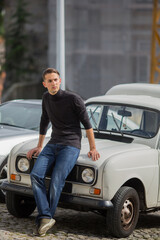 Young handsome fashionable man sitting on the hood of a vintage car.