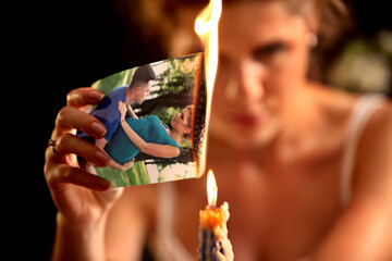 Broken heart woman. Couple break up. Sad bride on unhappy wedding. Woman and groom quarrel. Girl with vengeful look burns in fire candle family pictures. Portrait crying female.