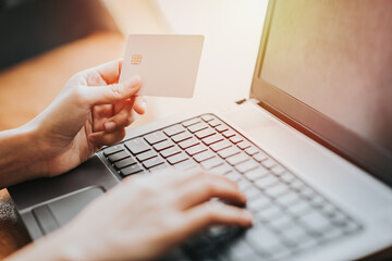 Hand holding credit card and using laptop for online business. shopping or online payment concept.