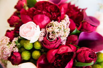 Engagement rings on beautiful wedding bouquet