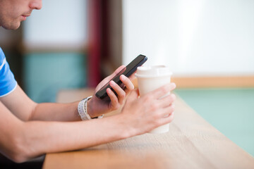 Cellphone and glass of coffee in cafe closeup. Man using mobile smartphone. Boy touching a screen of his smarthone.